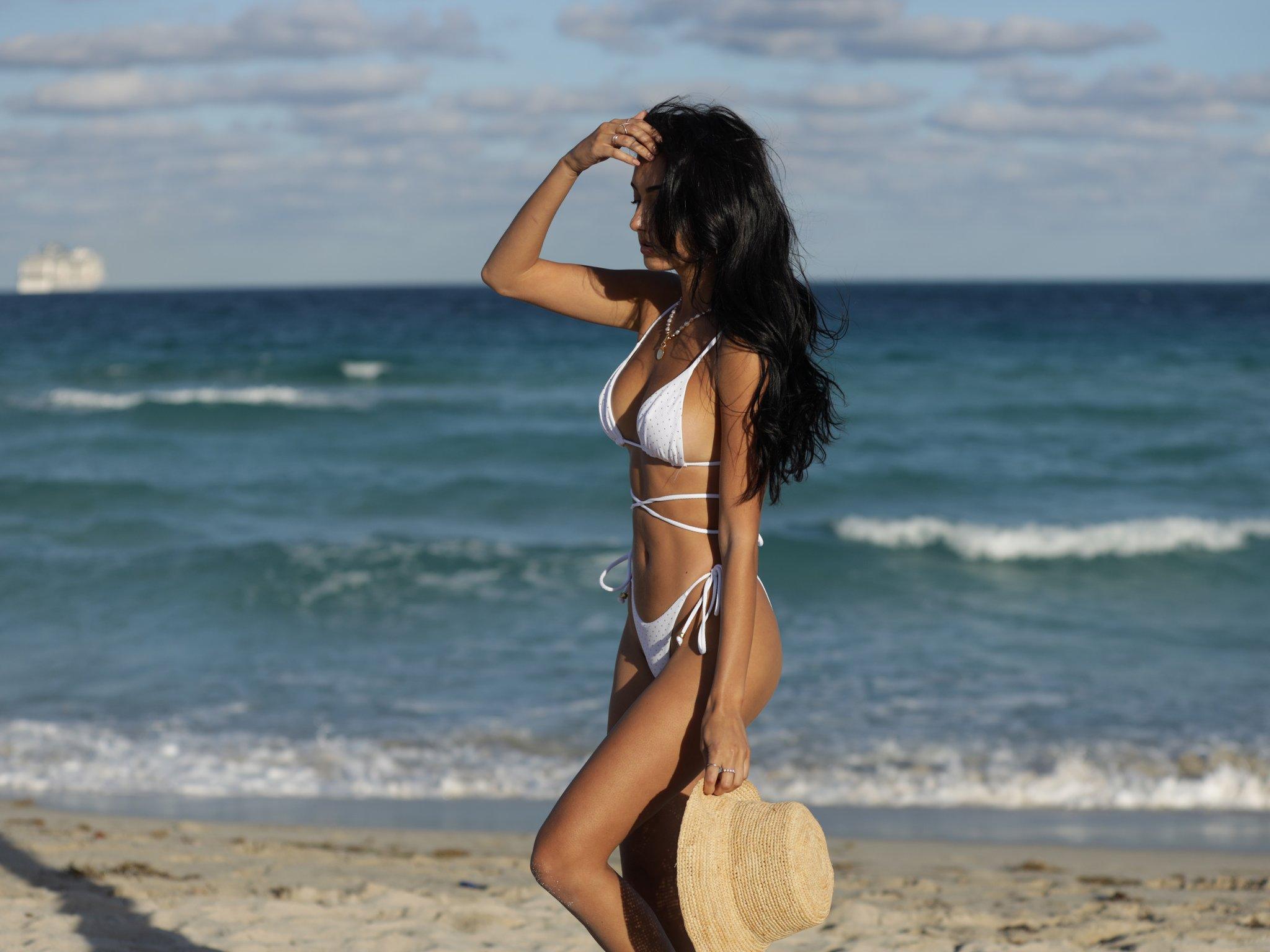 woman walking on a beach wearing a white bikini