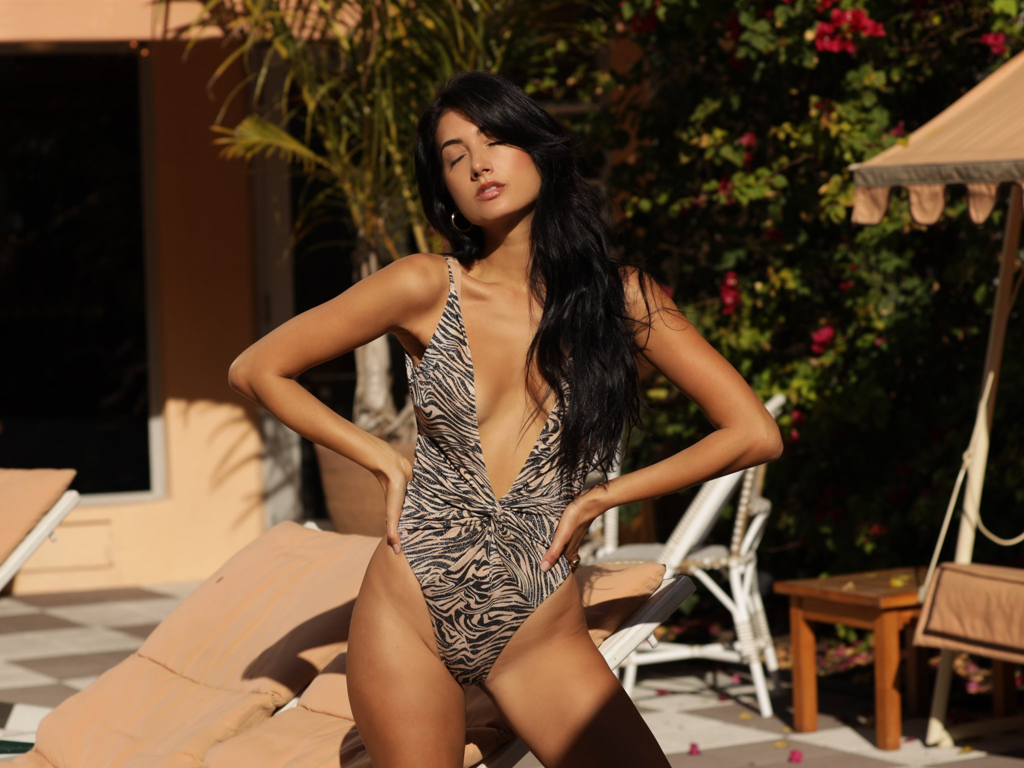 Woman standing in animal print one piece swimsuit
