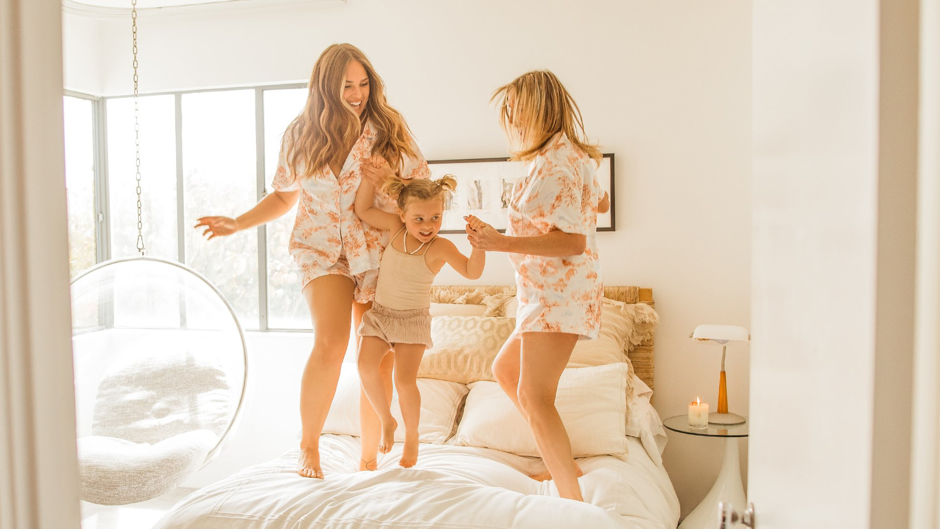 woman jumping on a bed with a child