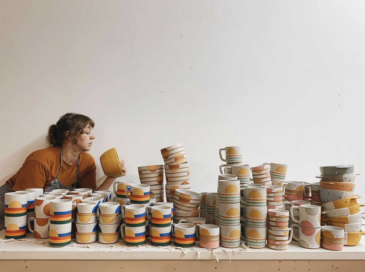 a woman with stacks of mugs